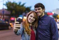 Молодая пара стоя на улице в сумерках города и принимая selfie — стоковое фото