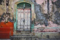 Worn and weathered facade of a building with peeling paint and double doors; Nicaragua — Stock Photo