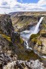 Женщина турист на краю скалы над водопадом долины Хайфосс, Исландия — стоковое фото