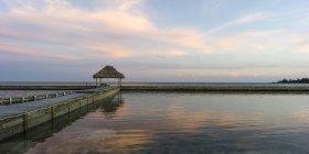 Panchina su un molo di fronte alla costa e l'oceano aperto all'alba, Belize — Foto stock