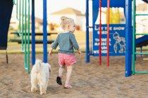 Заднього вигляду молодої дівчини і собака грають в ігровий майданчик — стокове фото