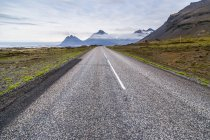 The long paved highway leading into the volcanic mountain landscape in the distance, Iceland — Stock Photo