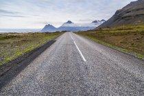 Die lange asphaltierte Straße führt in die vulkanische Berglandschaft in der Ferne, Island — Stockfoto