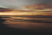 Le coucher de soleil lave l'or et l'orange sur l'océan et la plage, Long Beach, Californie, États-Unis d'Amérique — Photo de stock