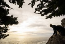 Man looking down over a rock to the ocean below at dusk — Stock Photo
