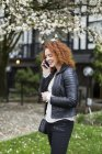 Woman talking on a cell phone while standing outside — Stock Photo