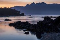 Al atardecer cae sobre la isla de Vancouver desde un islote en el Parque Provincial Nuchatlitz, Columbia Británica, Canadá - foto de stock