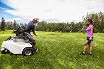 Um golfista fisicamente deficiente usando uma cadeira de rodas especializada teeing off e dirigindo uma bola no fairway de um campo de golfe, Edmonton, Alberta, Canadá — Fotografia de Stock