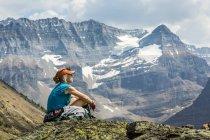 Жіночий турист сидить на скелястій місцевості з видом на гірський Віста у фоновому режимі; Британська Колумбія, Канада — стокове фото