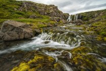 Прочный исландский ландшафт с ярко-зеленой тундрой и видом на побережье вдалеке; Исландия — стоковое фото