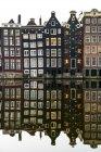 Façades de bâtiments avec un miroir réfléchissant dans un canal ; Amsterdam, Pays-Bas — Photo de stock