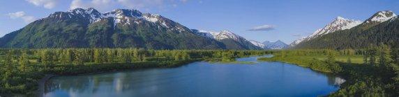 Живописные заснеженные Чугачские горы, отражающиеся в спокойной воде.; Анкоридж, Аляска, Соединенные Штаты Америки — стоковое фото