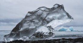 Pedaço de gelo em Diamond Beach, perto de Jokusarlon, com o oceano atrás dele ao longo da costa sul da Islândia; Islândia — Fotografia de Stock