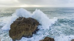 Large wave crashing into a rock along a coast. The biggest waves in the world are here in Nazare; Nazare, Leiria District, Portugal — Stock Photo