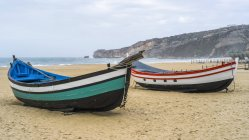 Two colourful, wooden rowboats on the beach in the seaside resort town of Nazare; Nazare, Leiria District, Portugal — Stock Photo