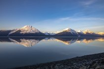 Turnagain Arm, South of Anchorage, Alaska in the morning. Ocean waters are calm and provides a good reflection of the mountains in the water; Alaska, United States of America — Stock Photo