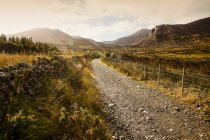 A gravel trail leads through a mountainous landscape at sunrise, Brandy Pad, Mourne Wall, Spellack, County Down, Ireland — Stock Photo