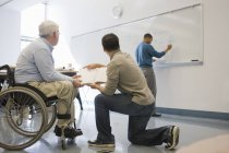 Professeur d'université avec Dystrophie musculaire enseignant aux étudiants dans une salle de classe — Photo de stock
