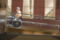 Профиль взрослого мужчины с мышечной дистрофией, сидящего в инвалидном кресле на рампе — стоковое фото