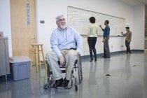 Professeur d'université avec des étudiants d'enseignement de dystrophie musculaire dans une salle de classe — Photo de stock