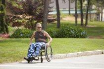 Homme avec blessure à la moelle épinière dans un passage à niveau en fauteuil roulant à pied accessible — Photo de stock