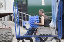Loading dock worker with spinal cord injury in a wheelchair moving stacked inventory trays — Stock Photo