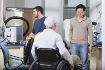 Professor with muscular dystrophy working with students in a laboratory — Stock Photo