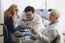 Professeur avec dystrophie musculaire travaillant avec des étudiants dans un laboratoire — Photo de stock