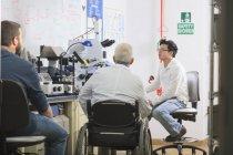 Professor com distrofia muscular trabalhando com alunos em laboratório — Fotografia de Stock