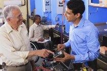 Estudante examinando sistema de controle elétrico em forno com professor em sala de aula HVAC um aluno em cadeira de rodas — Fotografia de Stock