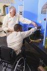 Инструктор обсуждает подзарядку кондиционера со студентом в инвалидной коляске в классе HVAC — стоковое фото