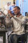 Студент в инвалидной коляске изучает печи воспламенителя в классе HVAC — стоковое фото
