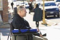 Человек с травмой спинного мозга и руки с повреждением нерва в моторизованной инвалидной коляске, переходящей улицу — стоковое фото