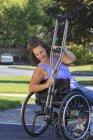 Жінка з Спіною Біфідою прикріпляє милиці до інвалідного візка. — стокове фото