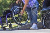 Donna con Spina Bifida con stampelle per mettere insieme la sedia a rotelle dopo aver viaggiato in auto — Foto stock