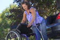 Жінка з Шпіною Біфідою за милицями розбирає крісло на колесах, щоб їхати в машині. — стокове фото