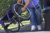 Donna con Spina Bifida usando le stampelle per smontare la sedia a rotelle per viaggiare in auto — Foto stock