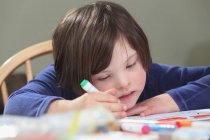 Child with Down Syndrome using coloring markers — Stock Photo