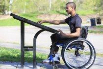 Чоловік, який переніс спінальний менінгіт у кріслі на колесах, читає каталог. — стокове фото