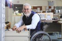 Людина з м'язовою дистрофією в інвалідному візку працює в офісі — стокове фото