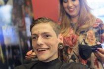 Homme à la mode avec une lésion de la moelle épinière dans un salon de coiffure se faire couper les cheveux — Photo de stock