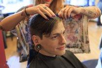 Homem na moda com uma lesão na medula espinhal em um salão de cabeleireiro recebendo um corte de cabelo — Fotografia de Stock
