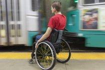 Модный человек с травмой спинного мозга в инвалидной коляске ждет поезда метро — стоковое фото