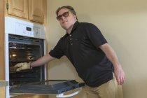 Uomo con cecità congenita che usa il forno nella sua cucina — Foto stock