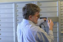 Homem com cegueira congênita abrindo sua caixa de correio em seu prédio de apartamentos — Fotografia de Stock