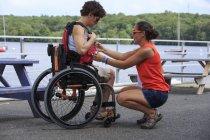 Femme avec une blessure à la moelle épinière aidée par un instructeur à utiliser un kayak — Photo de stock