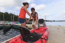 Instrutor ajudando uma mulher com uma lesão medular em um caiaque de sua cadeira de rodas — Fotografia de Stock