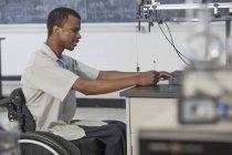 Студент з спінальним менінгітом у інвалідному візку вивчає прискорення на безфритовому столі в лабораторії. — стокове фото
