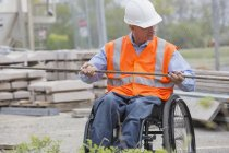 Инженер-проектировщик с травмой спинного мозга в инвалидной коляске на месте работы — стоковое фото