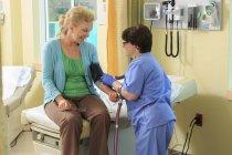 Медсестра з Церебралом Пальсі приймала кров'яний тиск у клініці. — стокове фото